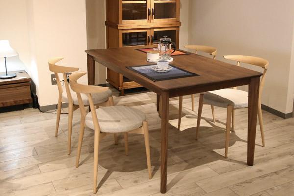明るい床に明るいチェアとウォールナットの家具を合わせた見た目